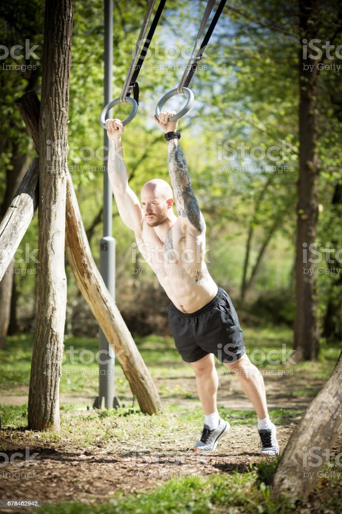 Muscular, topless  man on gymnastic rings, outdoor, public park royalty-free stock photo