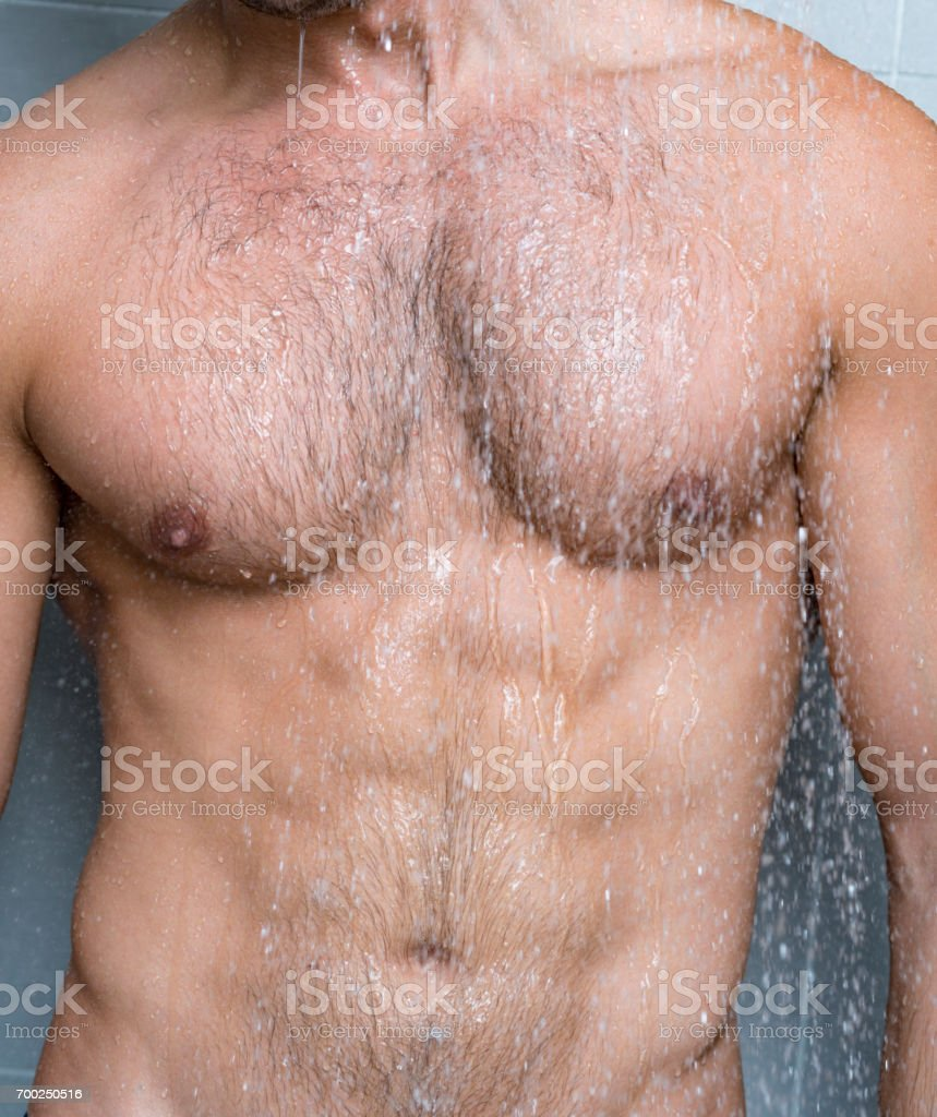 Muscular torso of 20's Man showering stock photo