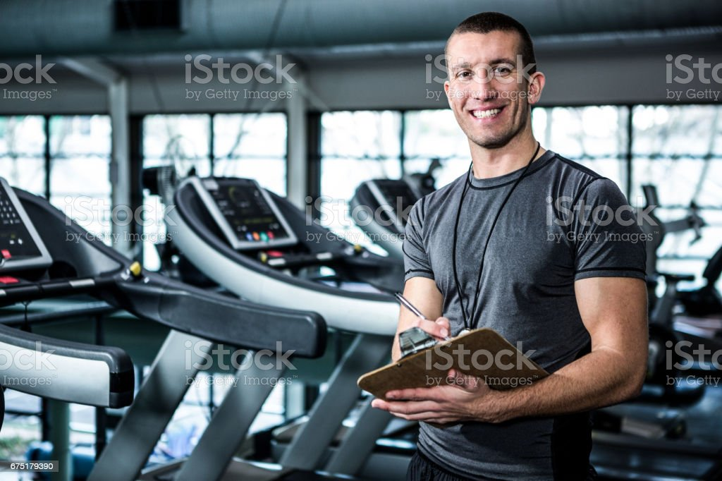 Muscular trainer writing on clipboard stock photo