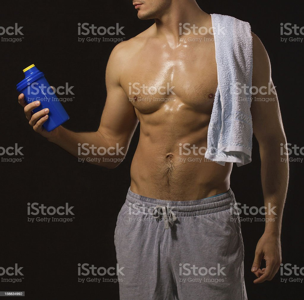 Muscular unrecognizable shirtless man with towel, isolated on black royalty-free stock photo