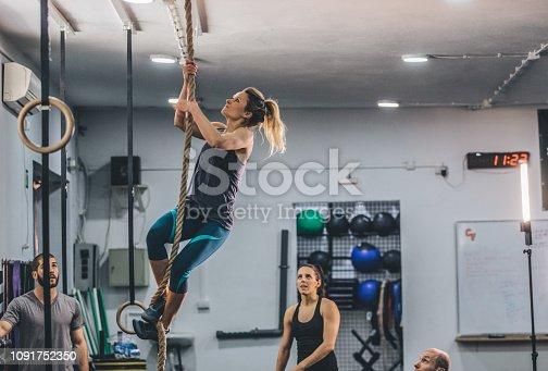 904150892 istock photo Muscular woman climbing rope 1091752350