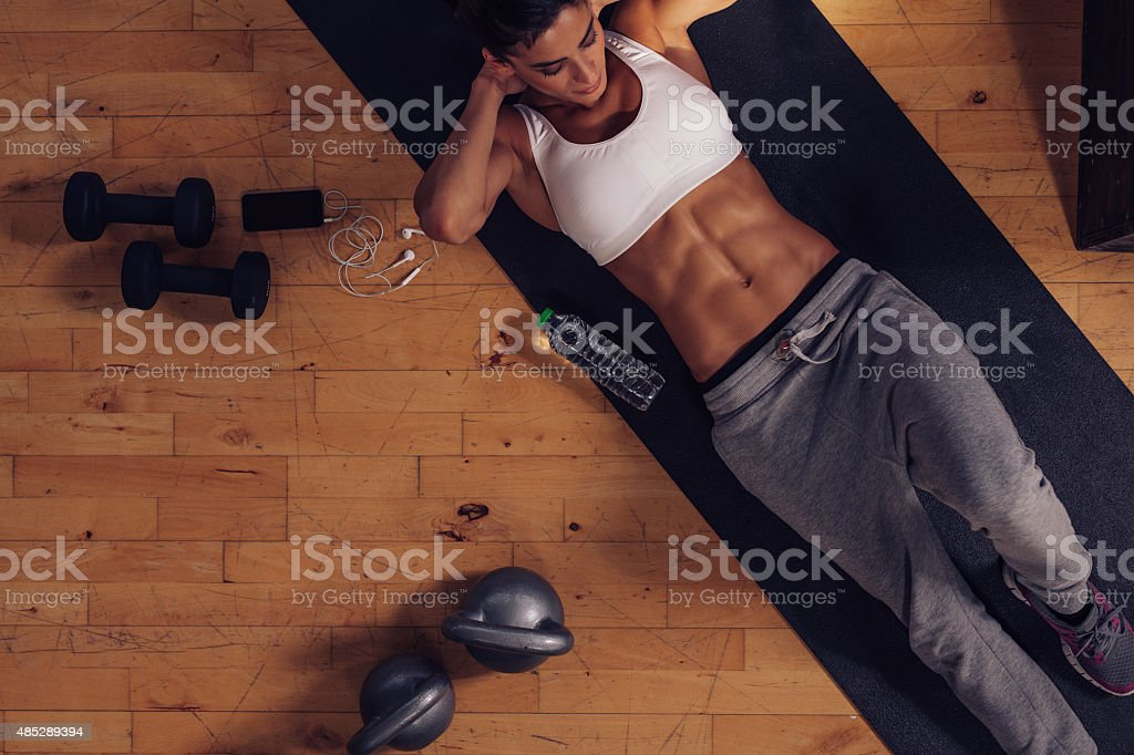 Muscular woman doing abs workout in gym stock photo