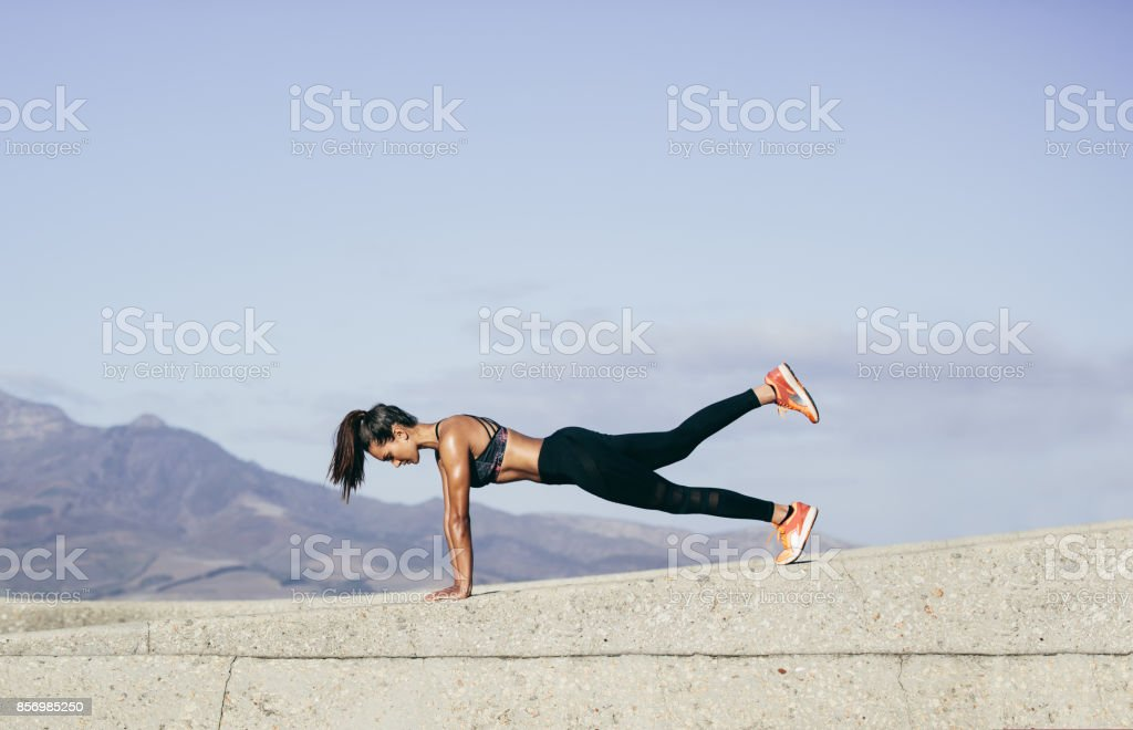 Muscular woman doing core exercise outdoors stock photo