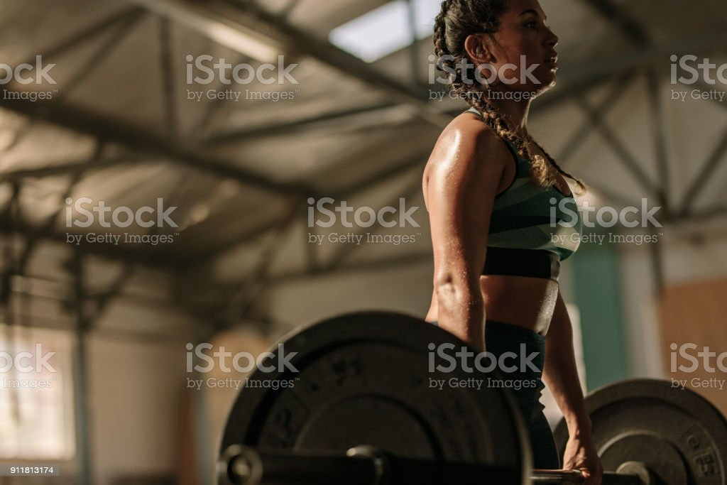 Muscular woman doing heavy weight exercises stock photo