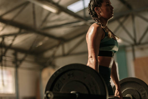 muscular woman doing heavy weight exercises - pesistica foto e immagini stock