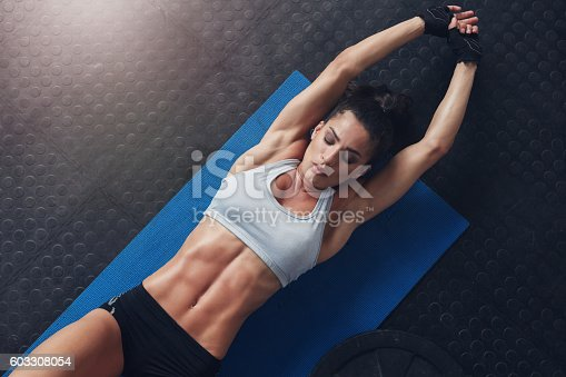 istock Muscular woman doing stretching workout on exercise mat 603308054