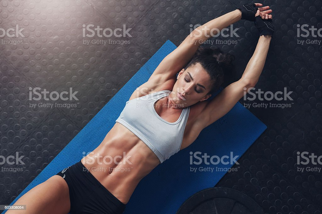 Muscular woman doing stretching workout on exercise mat stock photo
