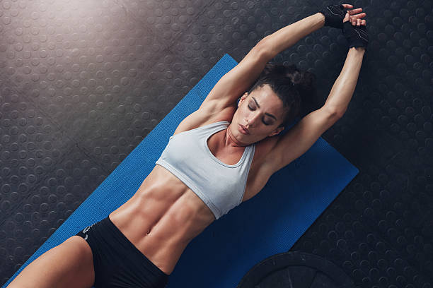muscular woman doing stretching workout on exercise mat - bauch übungen stock-fotos und bilder
