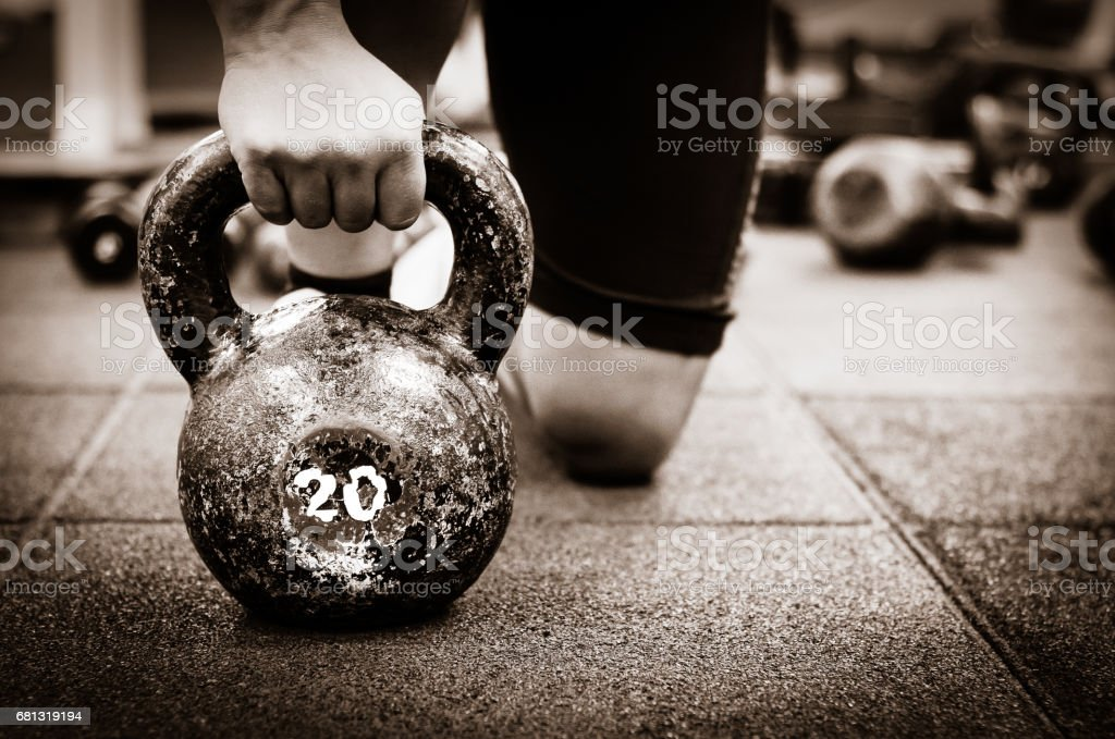 Muscular woman holding old and rusty kettle bell on to the gym floor. Dark image. royalty-free stock photo