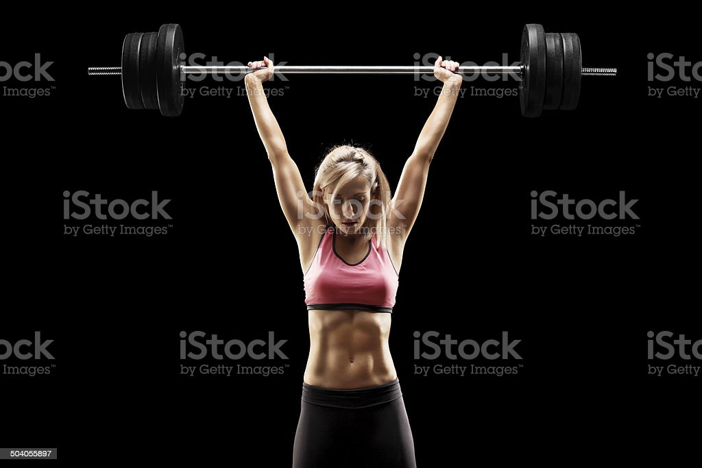 Muscular woman lifting a heavy barbell stock photo