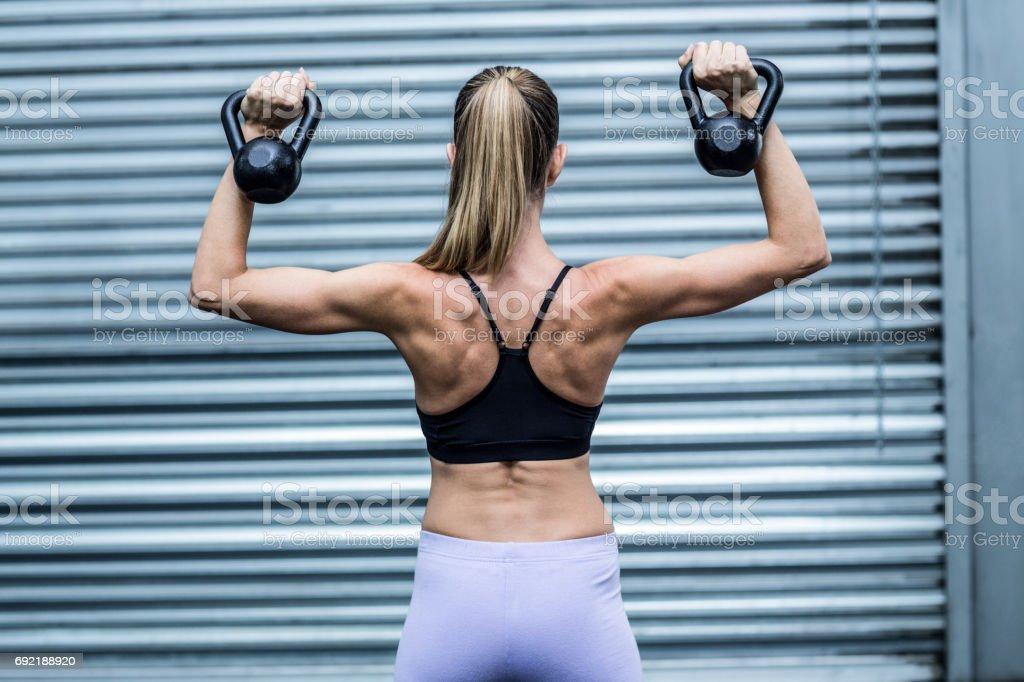 A muscular woman lifting kettlebells stock photo
