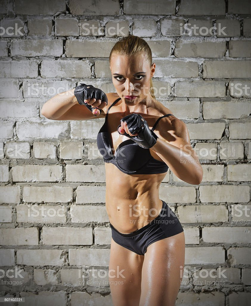 Muscular woman on brick wall (normal version) stock photo