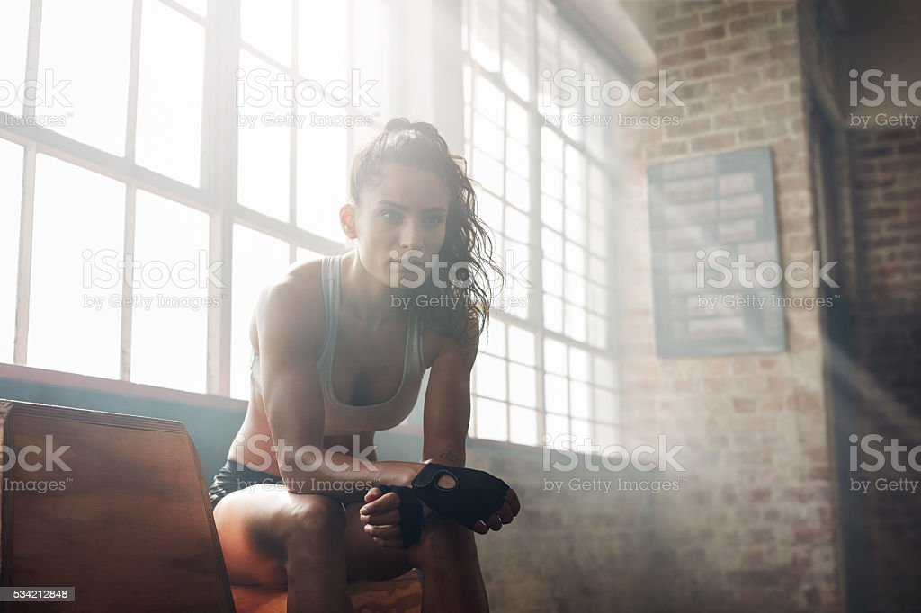 Muscular woman relaxing after workout at gym stock photo