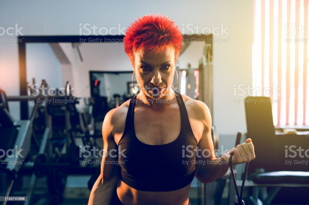 Muscular woman strong female athlete work out at the gym training...