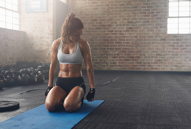 Muscular woman working out at the fitness club stock photo