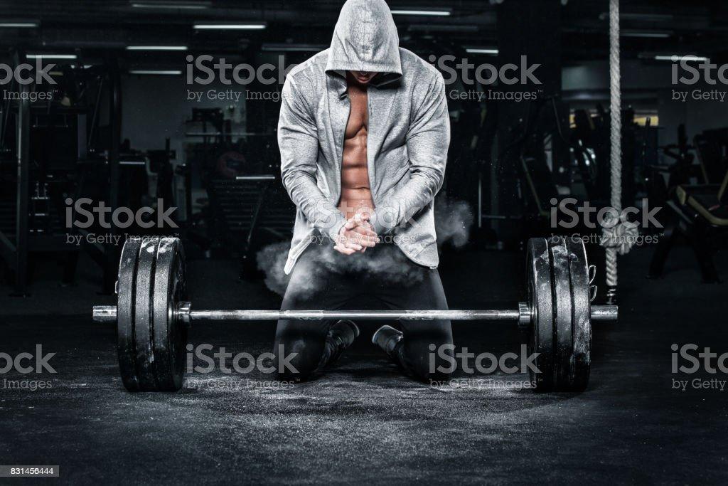 Entrenamiento de hombre de deportes fitness joven musculoso con barra en el gimnasio - foto de stock