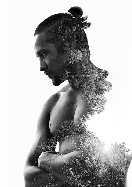 muscular young man and pine forest - männliche körperkunst stock-fotos und bilder