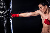 istock Muscular young man boxing in a gym 174810864