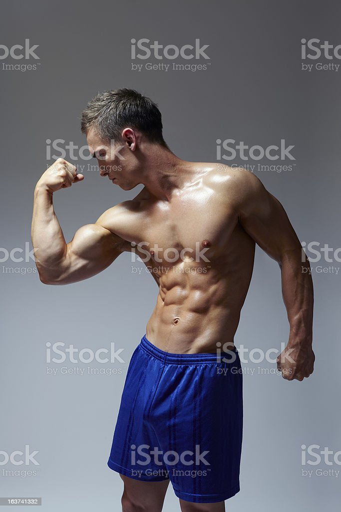 Muscular young man flexing arm muscles in sports outfit royalty-free stock photo