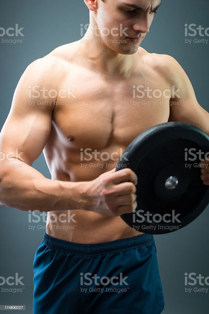 Muscular young man holding dumbbell . royalty-free stock photo