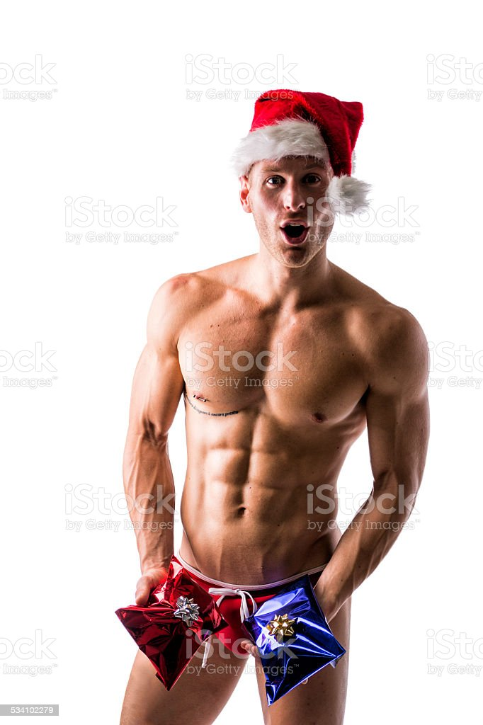 Muscular Young Man In A Speedo And Santa Claus Hat Stock Photo