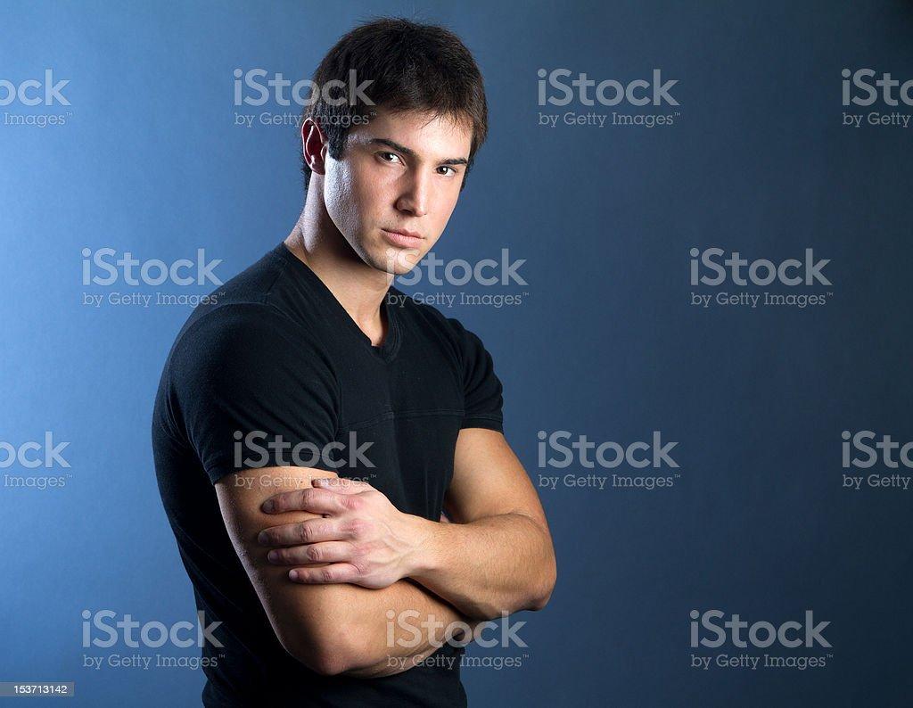 Muskuläre junger Mann im schwarzen t-shirt mit Farbverlauf, blau-schwarzen Hintergrund. – Foto