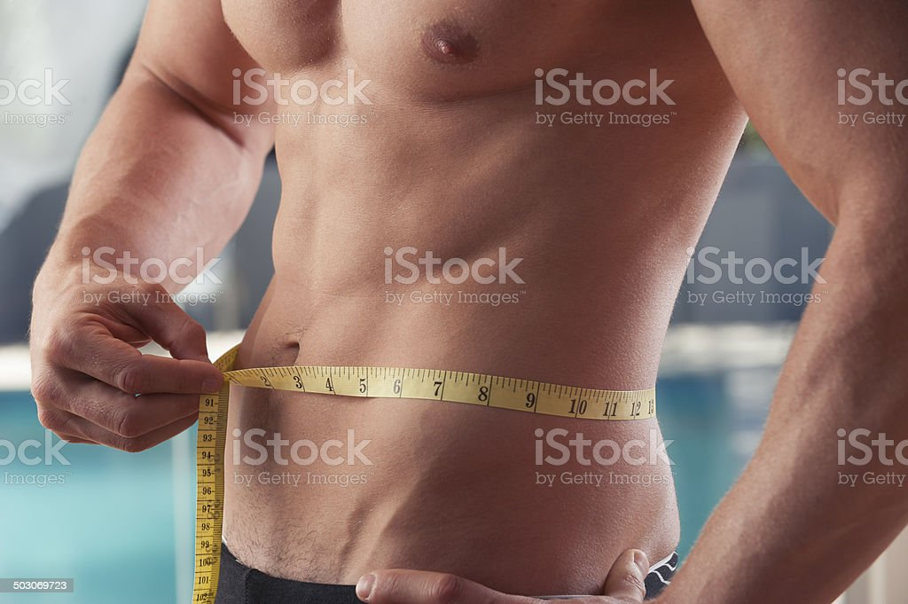 Muscular young man measuring waist royalty-free stock photo