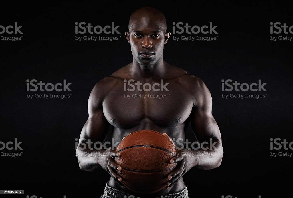 Portrait of muscular young man shirtless holding a basketball. Afro...