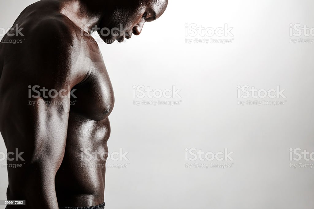 Muscular young man standing shirtless stock photo