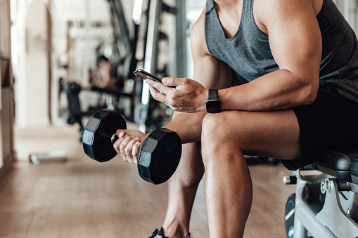 Close up shot of a young man lifting dumbbell while using smartphone. Bodybuilding motivation and determination.