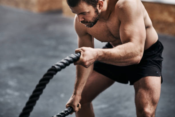 Muscular young man working out with ropes at the gym stock photo