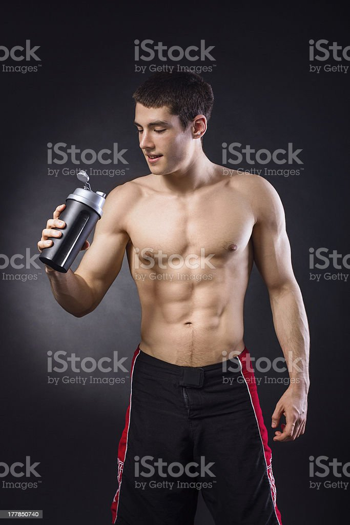 Muscular young shirtless man holding protein shake royalty-free stock photo