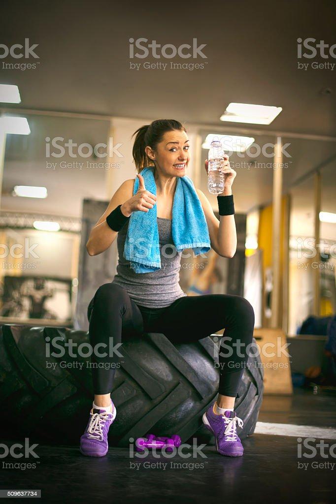 Muscular mujer joven atleta con agua - foto de stock