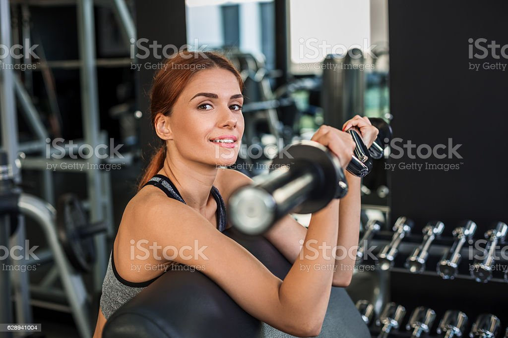 Muscular Young Woman Doing Exercises On The Simulator In The