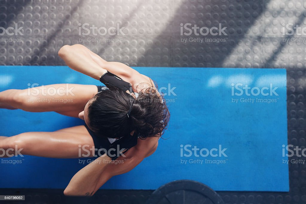 Muscular young woman doing sit ups on an exercise mat - Photo