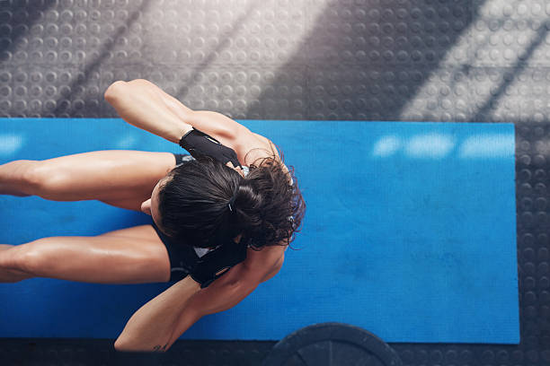 muscular young woman doing sit ups on an exercise mat - sit ups stock photos and pictures