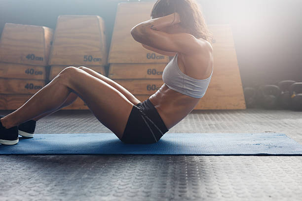 muscular young woman doing stomach exercises - sit ups stock photos and pictures