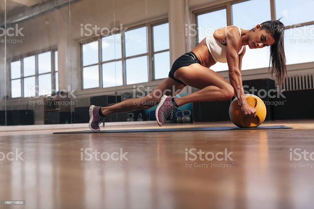 Muscular young woman doing workout at gym stock photo