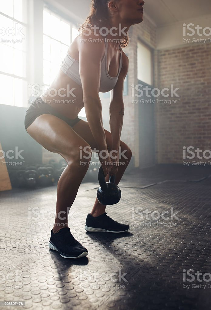Muscular young woman exercising with kettlebell stock photo