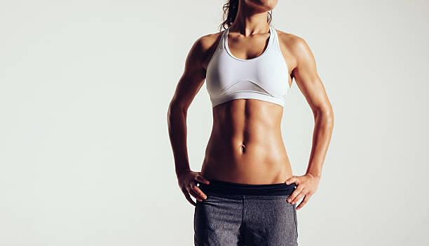 muskuläre junge frau posieren in sportswear - taillentrainer stock-fotos und bilder