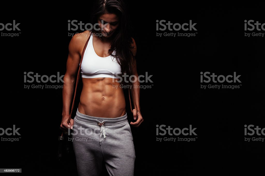 Muscular young woman with a jumping rope stock photo