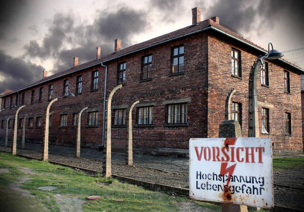 Museum Auschwitz - Birkenau. Warning sign high voltage. Barbed wire around a concentration camp. – zdjęcie