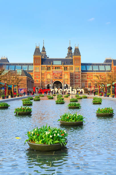 Museumplein Rijksmuseum, Amsterdam, Holland Amsterdam, Netherlands - March 31, 2016: Water and flowers, Rijksmuseum and people in front of writing, I amsterdam, Museumplein, Holland museumplein stock pictures, royalty-free photos & images
