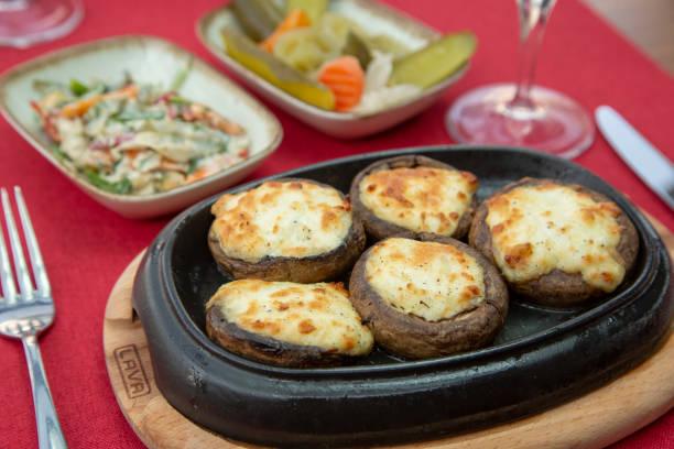 pilz und käse essen - gebackene champignons stock-fotos und bilder