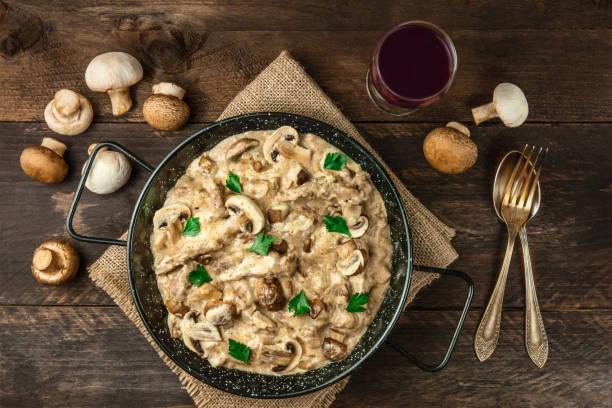 mushroom beef stroganoff mit rotwein auf rustikalen texturen - weinsoße stock-fotos und bilder