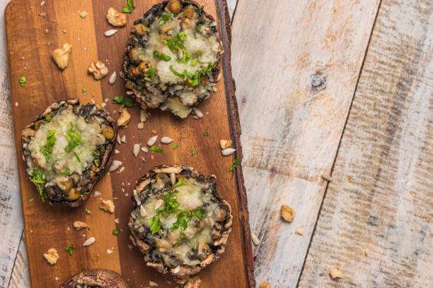 pilzköpfe gefüllt mit gemüse und käse - gefüllte zucchini vegetarisch stock-fotos und bilder