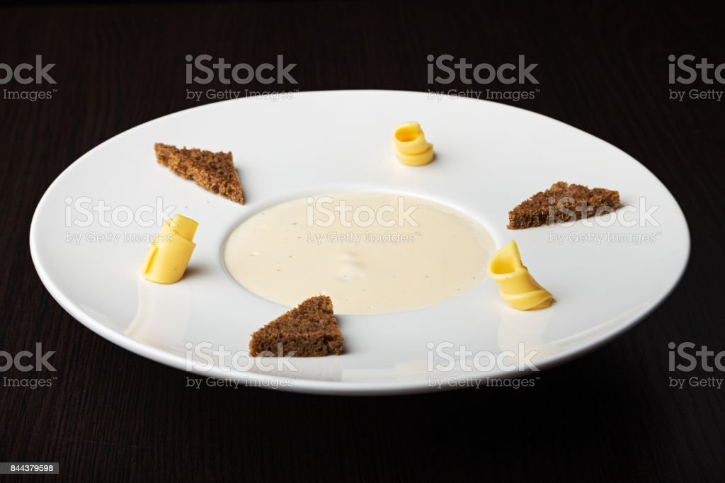 mushroom cream soup in white plate on a wooden table. on the edges of the plates are toasts rye bread and butter. stock photo