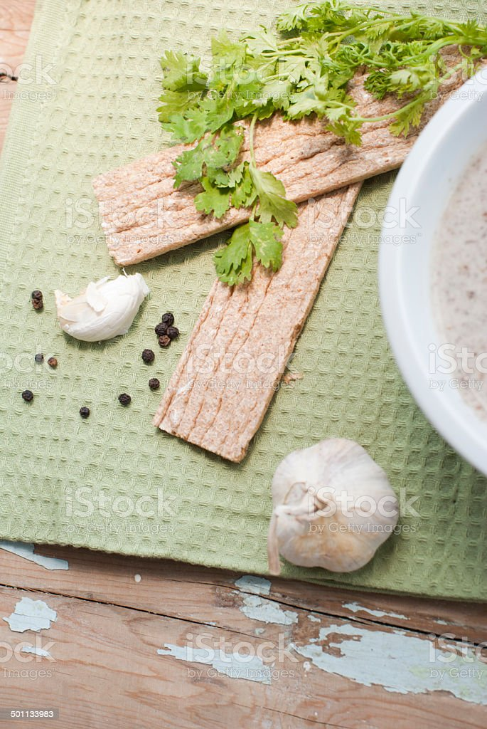Mushroom cream soup served with garlic and greens stock photo
