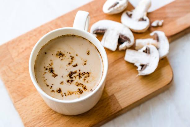 Café do latte do cogumelo com leite e café na placa de madeira pronta para beber. - foto de acervo