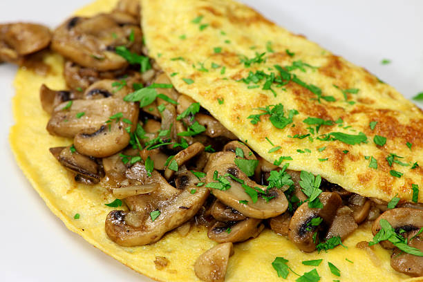 Mushroom omelet garnished with parsley on a white plate stock photo